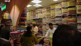 Dubai UAE - Januari 12, 2018: handelpaviljonger på tyg marknadsför i den nattDubai staden Sale arabiska tyger i lokal stock video