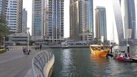 Dubai UAE - Januari 13, 2018: Turister som går på den Dubai marina Turist- träskepp i härlig kaj i Persiska viken lager videofilmer