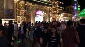 Dubai UAE - Januari 12, 2018: turistfolk som går och gör fotogränsmärket på mobiltelefonen på nattunderhållning stock video