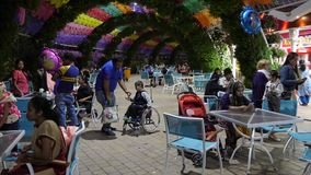 Dubai, UAE - January 18, 2018: arab people eating in evening outdoor cafe in Dubai Miracle Garden. Boy disabled in. Wheelchair dropped toy on floor and dad stock video