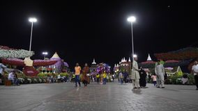 Dubai, UAE - January 18, 2018: arab people walking and resting in night in Dubai Miracle Garden. Night walking on. Background floral decoration in Miracle stock video footage