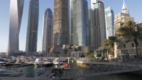 Dubai, UAE - January 18, 2018: luxury yacht and sea boat at parking lot in Dubai marina on background modern business. Skyscrapers in United Arab Emirates stock video footage