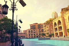 DUBAI UAE JULI 11, 2017: Ingången till det angränsande slotthotellet som omges av palmträd och den väldiga Burj khalifaen Arkivfoto