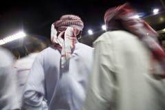 Dubai UAE liten grupp av traditionellt klädde muslimska män som strövar omkring jordning på Nad Al Sheba royaltyfria bilder