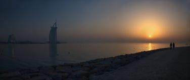 DUBAI, UAE - 30. MÄRZ 2017: Das Abendschattenbild mit dem Burj-Al Araber und Jumeirah setzen Hotels und die Paare auf dem Weg auf stockfotografie