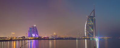 DUBAI, UAE - 30. MÄRZ 2017: Die Abendskyline mit dem Burj-Al Araber und Jumeirah setzen Hotels auf den Strand Lizenzfreies Stockbild