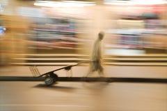Dubai UAE A man wheels an empty cart through the streets of Deira just after dark. Stock Image
