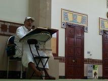 Dubai UAE - mars, 03, 2017: En man som läser Koranenboken i en moské i Dubai arkivbilder
