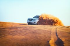 Off-road adventure with Nissan Patrol SUV in Arabian Desert at sunset. Offroad vehicle bashing through sand dunes royalty free stock photography