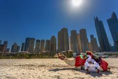 DUBAI UAE - OKTOBER 11: Beduin med kamel på stranden på Jum Royaltyfri Bild