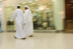 Dubai UAE Two men traditionally dressed in dishdashs and gutras white robes and headdresses. Royalty Free Stock Photography