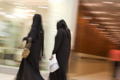 Dubai UAE Two women dressed in traditional abayas and hijabs black robes and scarves. Royalty Free Stock Image