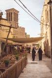 Dubai, United Arab Emirates - 28 de marzo de 2019: Una de las calles de Al Seef Heritage District con caminar a mujeres árabes imágenes de archivo libres de regalías