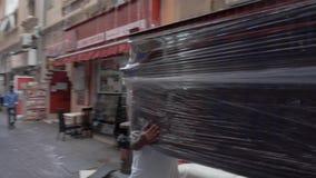 Loaders carry sofa along pedestrian street past shops. DUBAI UNITED ARAB EMIRATES - DECEMBER 18 2018: Arabian loaders carry sofa covered with plastic on heads stock video footage