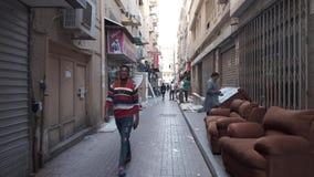 Men walk along pedestrian street with open and closed shops. DUBAI UNITED ARAB EMIRATES - DECEMBER 18 2018: Camera moves along narrow pedestrian street past stock video