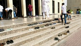 Muslims going in to a mosque. DUBAI, UNITED ARAB EMIRATES - DECEMBER 22, 2018: Islamic Traditions. Muslims removes their shoes before going in to a mosque stock video footage