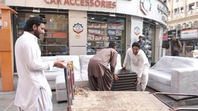 Arabian workers unload furniture greet tourists in street. DUBAI UNITED ARAB EMIRATES - DECEMBER 18 2018: Smiling Arabian shop workers in white clothes unload stock footage