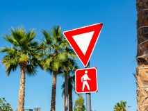 Dubai, United Arab Emirates - December 12, 2018: Yield To Pedestrians Sign in red frames against the blue sky and palm royalty free stock images