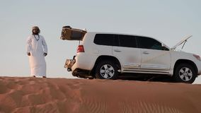 Low angle shot arabian man stands by jeep on dune top. DUBAI UNITED ARAB EMIRATES - JANUARY 08 2019: Low angle shot arabian man in national white clothes stands stock video