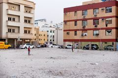 Children playing a game of cricket. Dubai, United Arab Emirates, June 8, 2013: Children playing a game of cricket on a vacant sandy block in Dubai royalty free stock photos