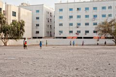 Children playing a game of cricket. Dubai, United Arab Emirates, June 8, 2013: Children playing a game of cricket on a vacant sandy block in Dubai stock images