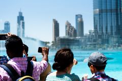Dubai, United Arab Emirates - March 26, 2018: People gather around the Dubai mall fountain to see the water show. Which attracts many tourist every day stock photography