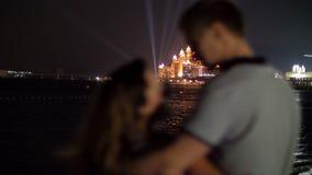 DUBAI, UNITED ARAB EMIRATES, UAE - NOVEMBER 20, 2017: Atlantis The Palm, Dubai . Atlantis hotel iluminated at night. Couple in love admires the beauty of the stock video footage