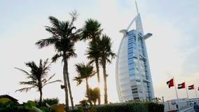 DUBAI, UNITED ARAB EMIRATES, UAE - NOVEMBER 20, 2017: Hotel Burj al Arab , at sunset, palms are seen, flags are. DUBAI, UNITED ARAB EMIRATES, UAE - NOVEMBER 20 stock video