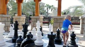 DUBAI, UNITED ARAB EMIRATES, UAE - NOVEMBER 20, 2017: Hotel Jumeirah Al Qasr Madinat , baby boy playing big outdoors. DUBAI, UNITED ARAB EMIRATES, UAE - NOVEMBER stock footage