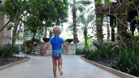Dubai, United Arab Emirates, Uae - November 20, 2017: Hotel Jumeirah Al Qasr Madinat , baby boy runs through the hotel. Garden, he is happy stock footage