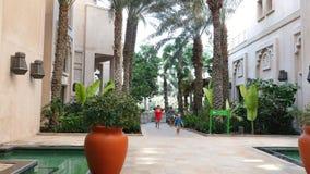 DUBAI, UNITED ARAB EMIRATES, UAE - NOVEMBER 20, 2017: Hotel Jumeirah Al Qasr Madinat , Mom and child walk from the beach. Through the territory of the hotel stock video