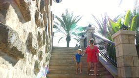 DUBAI, UNITED ARAB EMIRATES, UAE - NOVEMBER 20, 2017: Hotel Jumeirah Al Qasr Madinat , mom and son walking around hotel. Descend the stairs in the rays of the stock footage