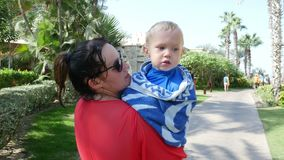 Dubai, United Arab Emirates, Uae - November 20, 2017: Hotel Jumeirah Al Qasr Madinat, mother carries a wet little boy. Wrapped in a towel. he is cold stock video footage