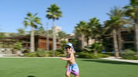 DUBAI, UNITED ARAB EMIRATES, UAE - NOVEMBER 20, 2017: Hotel Jumeirah Al Qasr Madinat, near Burj al Arab. little boy. Running happily on a green lawn stock video footage