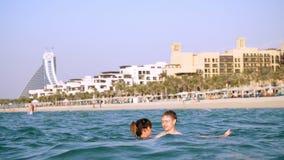 DUBAI, UNITED ARAB EMIRATES, UAE - NOVEMBER 20, 2017: Hotel Jumeirah Al Qasr Madinat, near Burj al Arab. a pair of young. People swim in the water, hug, have stock video