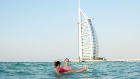 DUBAI, UNITED ARAB EMIRATES, UAE - NOVEMBER 20, 2017: Hotel Jumeirah Al Qasr Madinat, near Burj al Arab. a pair of young. People swim in the water, hug, have stock video footage