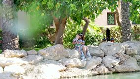 DUBAI, UNITED ARAB EMIRATES, UAE - NOVEMBER 20, 2017: Hotel JUMEIRAH Madinat, on the bank of artificial canal, mother. With baby daughter sit, admire the stock video