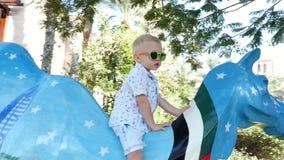 Dubai, United Arab Emirates, Uae - November 20, 2017: Hotel Jumeirah Madinat , a boy, child climbed onto colored statue. Of a camel stock footage