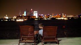 Dubai, United Arab Emirates, Uae - November 20, 2017: hotel Sofitel The Palm, Dubai . skyscrapers iluminated at night. Couple in love admires the beauty of the stock video footage