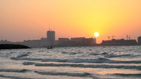 DUBAI, UNITED ARAB EMIRATES, UAE - NOVEMBER 20, 2017: at sunset, the surf. waves roll on the sand and spread over it. Outlines of city houses are visible in stock footage