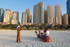 DUBAJ, UAE - LISTOPAD 23, 2017: Turyści jadą wielbłądy przed Jumeirah Beach Residence w Dubaj, Zjednoczone Emiraty Arabskie Dubaj obrazy royalty free