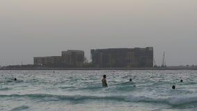 Dubaj wieczór swimers z palmy hotelową budową przeglądają 4k uae zbiory
