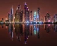 DUBAJ, ZJEDNOCZONE EMIRATY ARABSKIE - 23 PAŹDZIERNIK, 2014: Nowożytny nocy miasto Dubaj, z odbiciem na wody powierzchni Obrazy Royalty Free