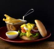 Dubbel BBQ-nötkötthamburgare med pommes frites & doppsås royaltyfri bild