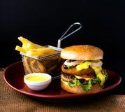 Dubbel BBQ-nötkötthamburgare med pommes frites & doppsås royaltyfri foto