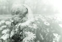 Dubbel blootstellingsbeeld van een kleine van de blondemeisje en lente weide stock foto