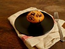 Dubbel choklad Chip Muffin på plattan och servett Arkivbild