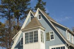 Dubbel-een hoogtepunt bereikt dak van blauw familiehuis Stock Foto