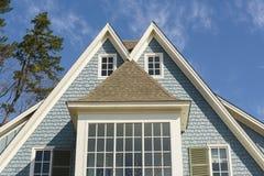 Dubbel-een hoogtepunt bereikt dak van blauw familiehuis Stock Afbeeldingen