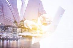Dubbel explosure med affärsmän som arbetar med bärbara datorn och natt Arkivfoto